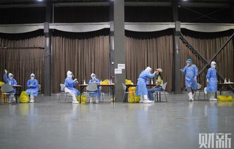 2020年6月17日,北京朝阳公园,身着防护服的医护人员对居民进行核酸测试。图/财新记者 丁刚