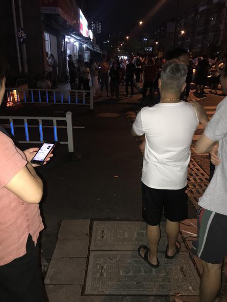 (24日夜,大量居民聚集小区门口议论此事)