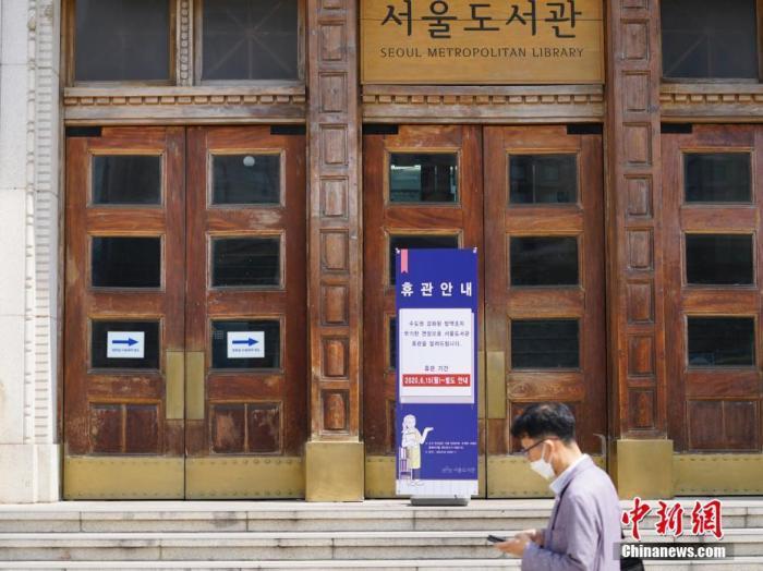 6月23日,一位韩国首尔市民经过首尔市立图书馆门前,该图书馆贴出闭馆通知。近来,包括韩国首尔、仁川、京畿道在内的首都圈确诊病例持续增加。中新社记者 曾鼐 摄