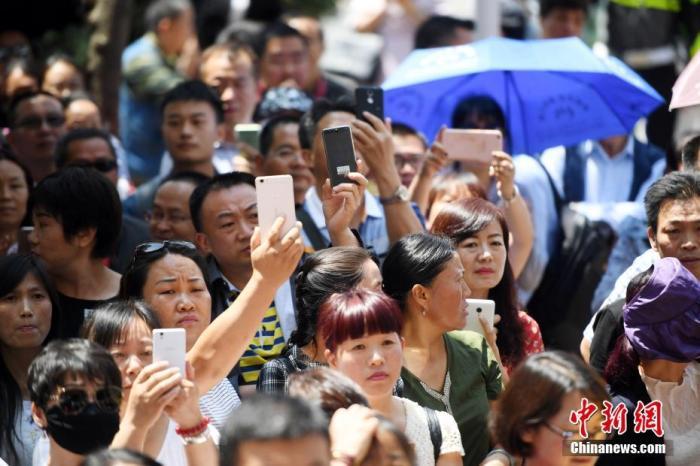 资料图:2017年6月7日,昆明市五华考区云大附中考点,上午的考试结束前在门口等候考生的家长们举着手机给孩子拍照。中新社记者 李进红 摄
