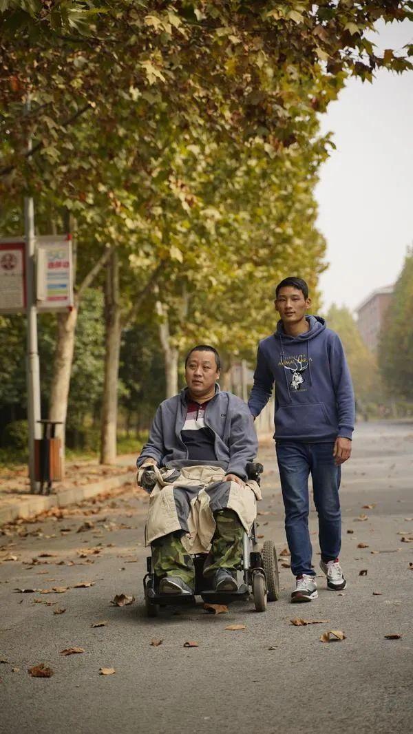 马永恩推着父亲在校园散步。图片来源:河南商报