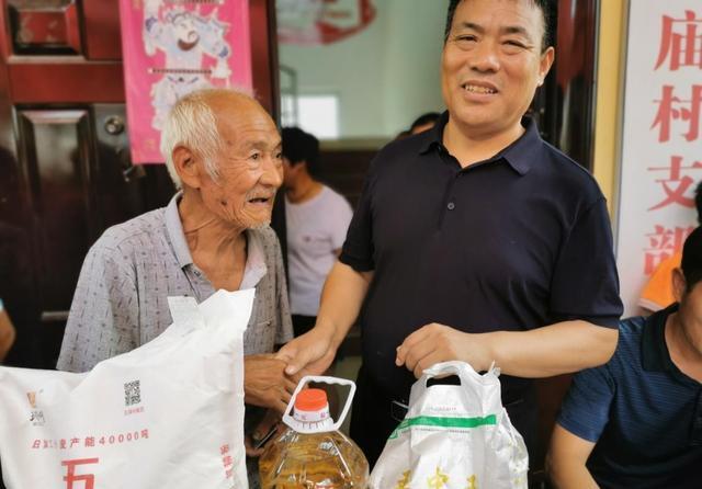赵丽祥(左二)为老年人发放礼品 (王向灵摄)
