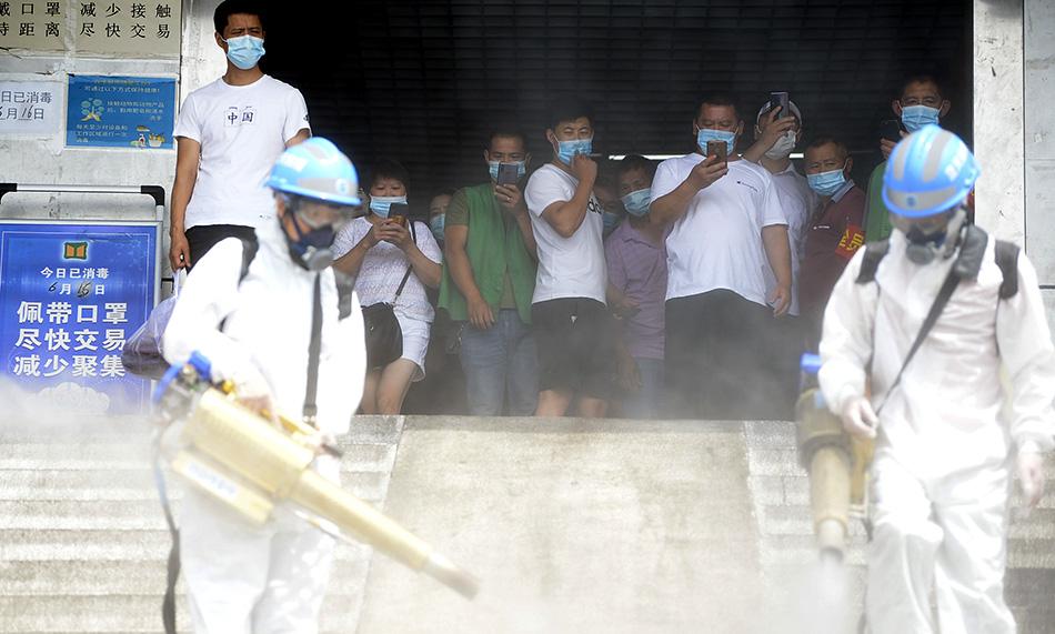 6月16日,北京蓝天救援队队员们身穿防护服、头戴安全帽和护目镜,身上背着药水壶,手持弥雾枪,全副武装对岳各庄批发市场消杀。人民视觉 图