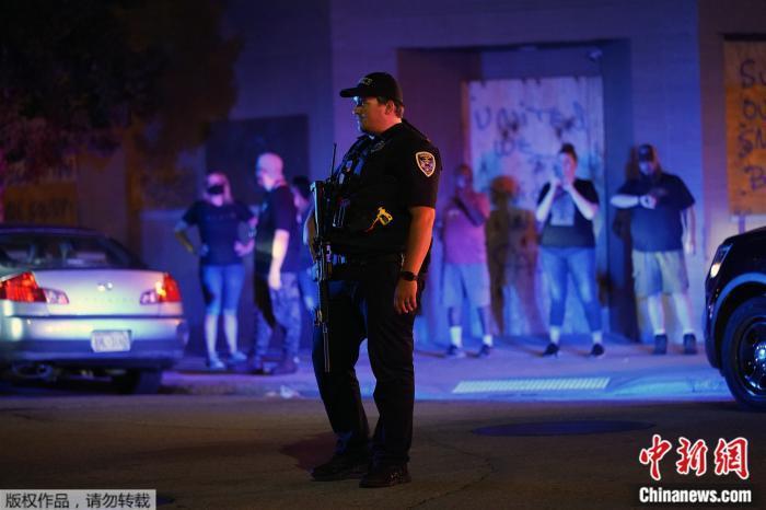 当地时间2020年8月25日,美国威斯康星州基诺沙,一名警察站在抗议者聚集的街道上。