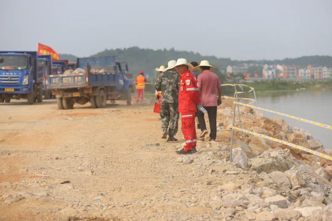 为填满决口,运料车需要不间断运来大石块倒入河中。