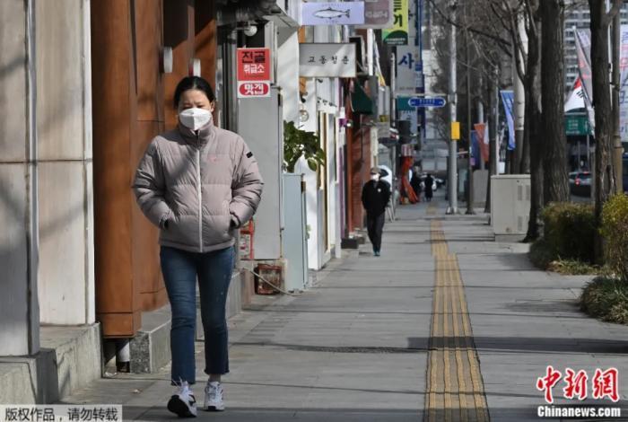 2020年2月27日,一名女子戴着口罩走在韩国大邱街道上。