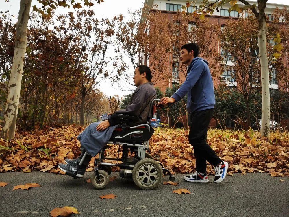 马永恩推着父亲在校园散步。(王兴辉 摄)