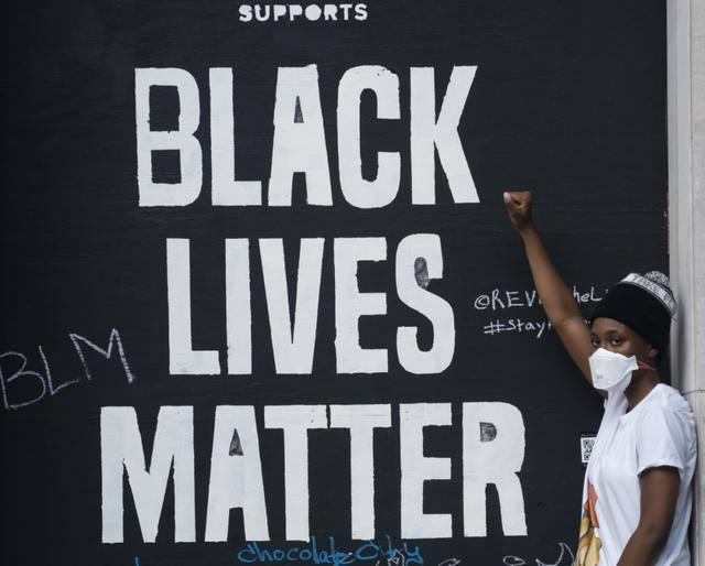 """(图说:6月19日,在美国首都华盛顿白宫附近,一名女孩参加集会游行期间与墙上的标语""""黑人的命也是命""""合影。图源/新华社)"""
