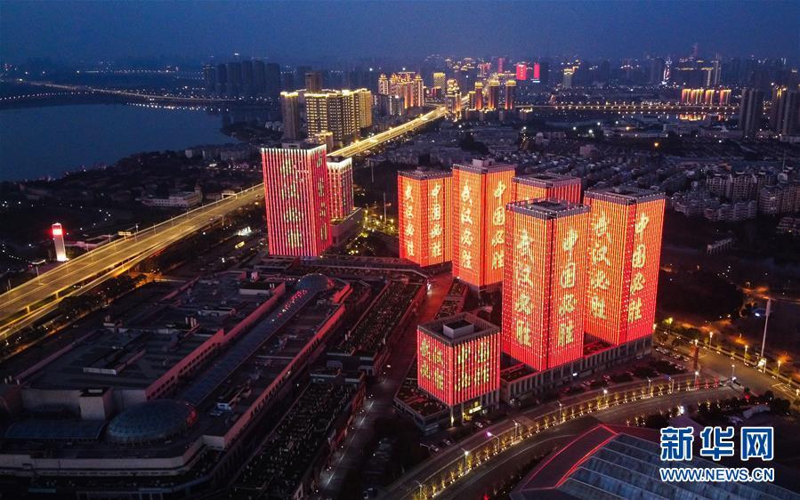 """2月12日,武汉体育中心附近高层建筑外墙打出""""武汉必胜""""等字样。(图/新华社)"""