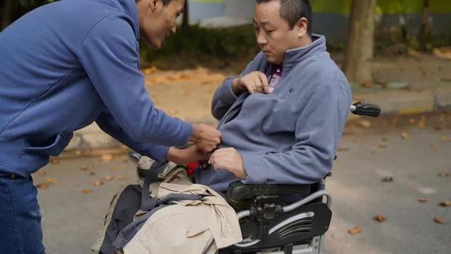 马永恩为父亲穿外套。图片来源:河南商报