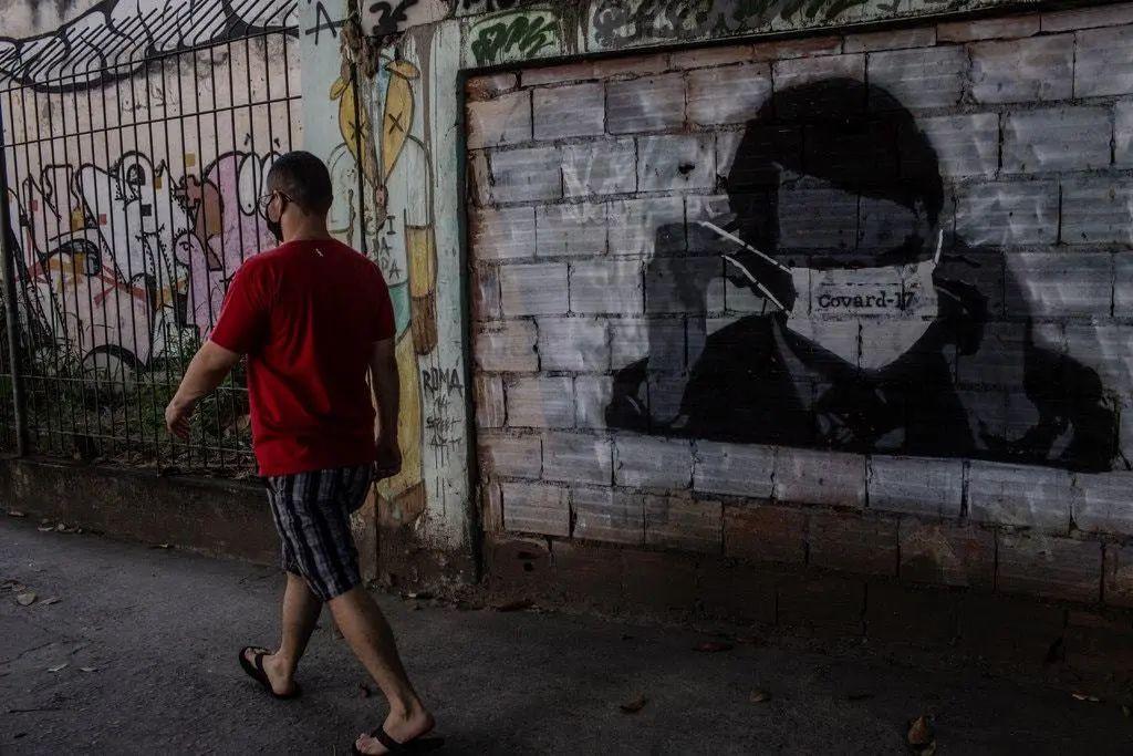 """里约热内卢的一幅反博索纳罗壁画显示,总统戴着一副用葡萄牙语写""""胆小鬼""""的口罩,玩着"""" Covid""""一词"""