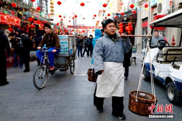 """资料图:此前,以""""品京味赏民俗情思大栅栏""""为主题的民俗风情展在北京大栅栏西街开幕。中新社发 富田 摄"""