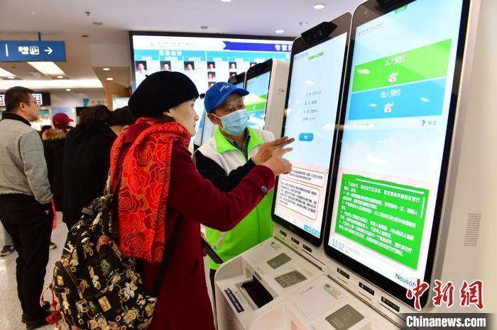 资料图:一位患者在指导下使用人脸识别系统预约专家号。 王广兆 摄