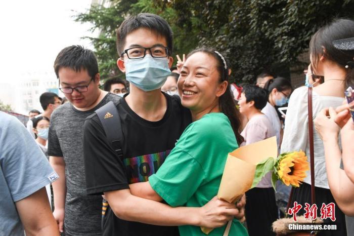 7月8日,山西太原一高考考点外,家长与走出考场的考生拥抱庆祝。 中新社记者 武俊杰 摄