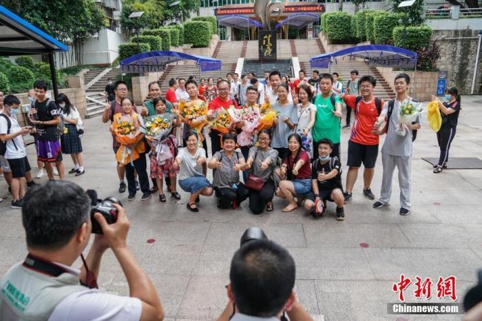 7月8日下午,广西南宁二中新民校区考点,高考英语科目考试结束后,老师与考生在考场外合影留念。中新社记者 陈冠言 摄