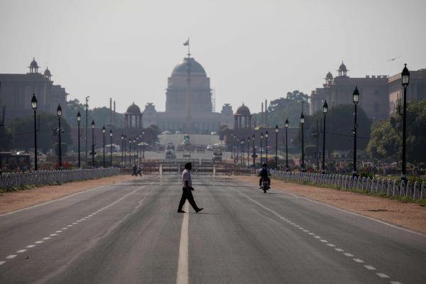 3月22日,在印度新德里,一名男子穿过空旷的马路。(新华社 法新)