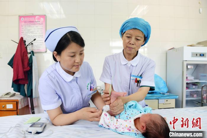 资料图:医护人员照顾婴儿。 孙莹 摄