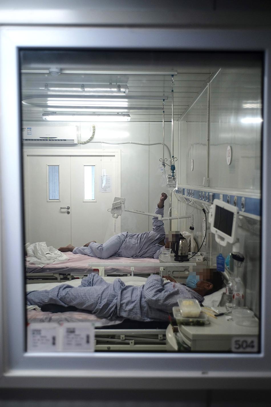 6月16日,一名患者在北京地坛医院隔离病房内打电话。彭子洋/新华社 图
