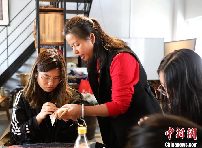 广西苗族刺绣代表性传承人李伊园在指导学生练习刺绣。 韦鼎标 摄