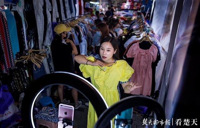 江汉路上的地摊主一边摆地摊一边直播,图片来源:楚天都市报