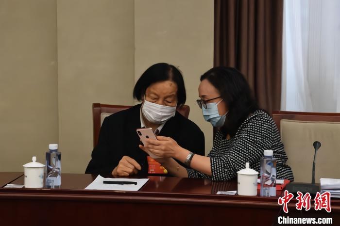 全国两会期间,杨林花和申纪兰探讨交流。 受访者供图 摄