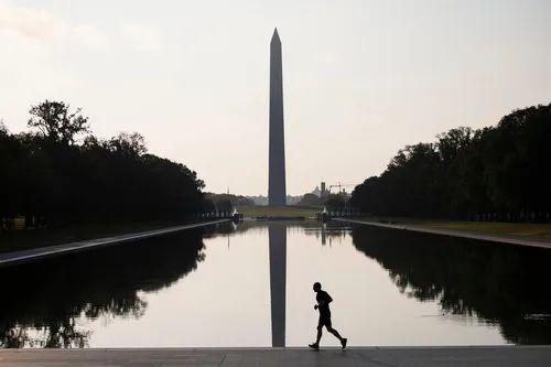 7月8日,在美国华盛顿,一名男子跑步经过林肯纪念堂倒影池。新华社记者 刘杰 摄