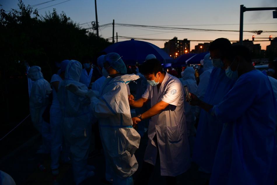6月15日,夜色下,北京丰台区一处咽拭子样本采集点,工作人员在整理防护服。人民视觉 图
