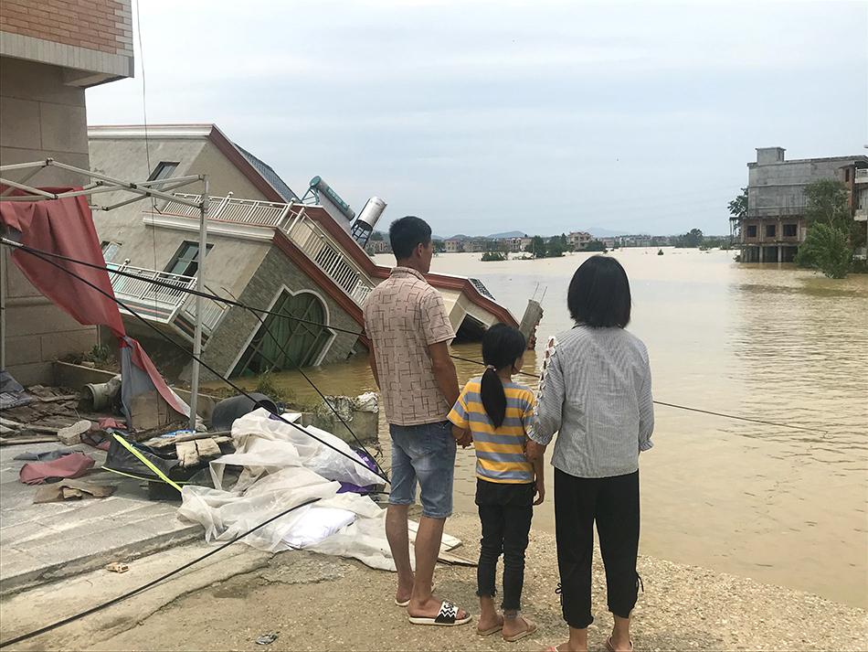 黄紫益和妻子女儿来到决堤处,他们家的房子已经被冲走,隔壁叔叔家的房子倾斜在水中