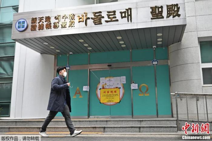 """资料图:韩国一名男子戴着口罩,走过首尔一""""新天地""""教会的分部,该分部已被政府查封。"""