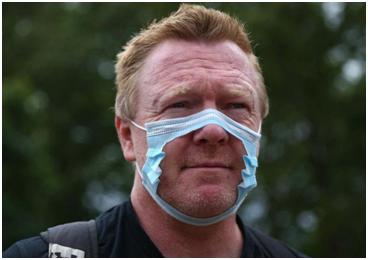 抗议现场,有示威者戴着被剪出洞的口罩 图源:《独立报》