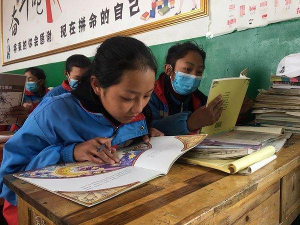 青海一所私塾的弟子正在浏览新东方施舍的书籍
