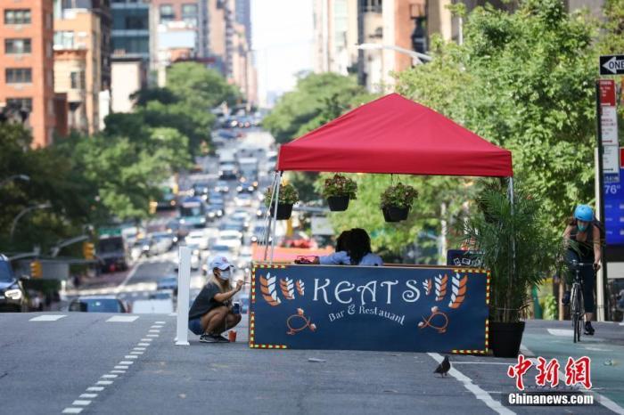 当地时间7月16日,美国纽约曼哈顿,一家餐厅的做事人员在安放户表就餐区。因防疫必要,纽约市正本答在第三阶段盛开的餐饮业室内就餐仍处于止息状态,当局鼓励餐厅申请竖立户表就餐区。中新社记者 廖攀 摄