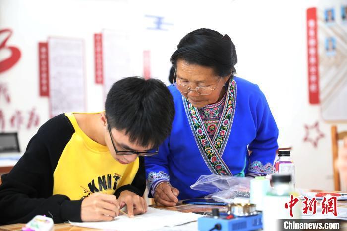 广西苗族蜡染传承人梁桂花指导学生进行蜡染制作。 韦鼎标 摄