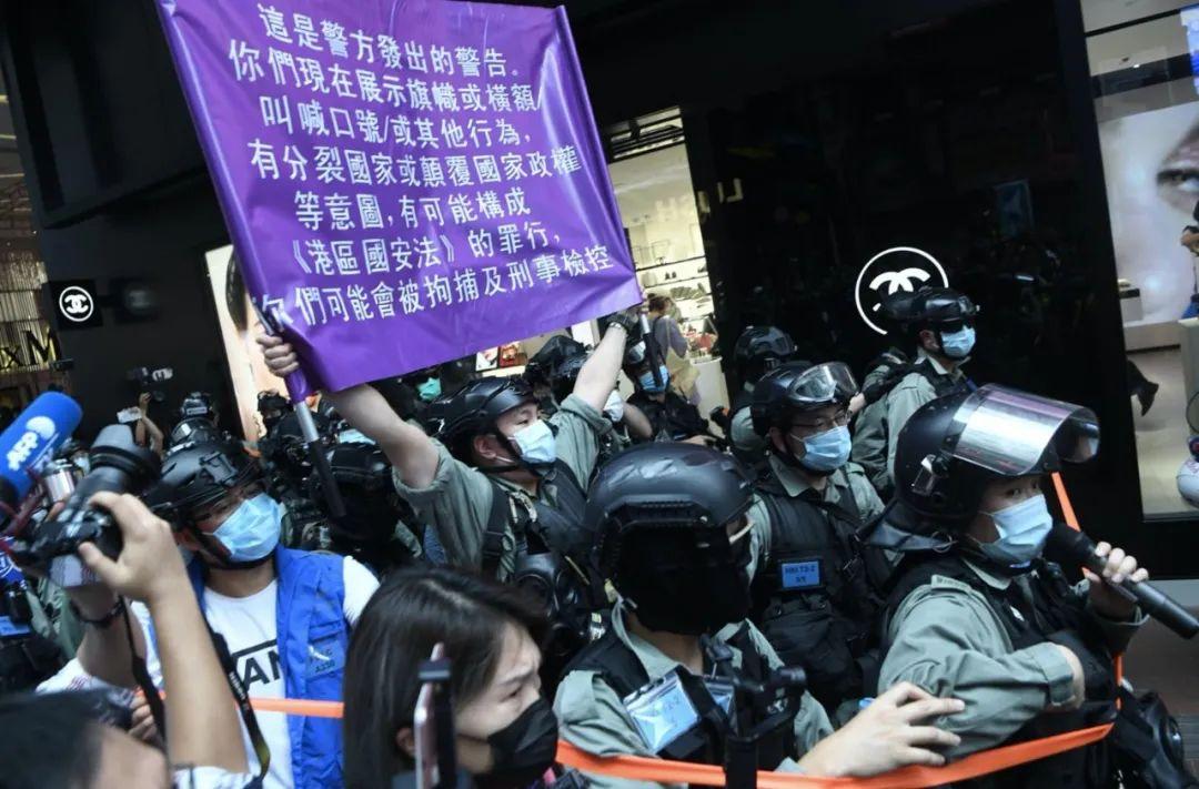 港区国安法已于6月30日23时刊宪生效。7月1日起,香港警务人员将加强实时执法。图为7月1日当天香港警察高举紫色警告旗执法。(图源:港警官方Facebook)