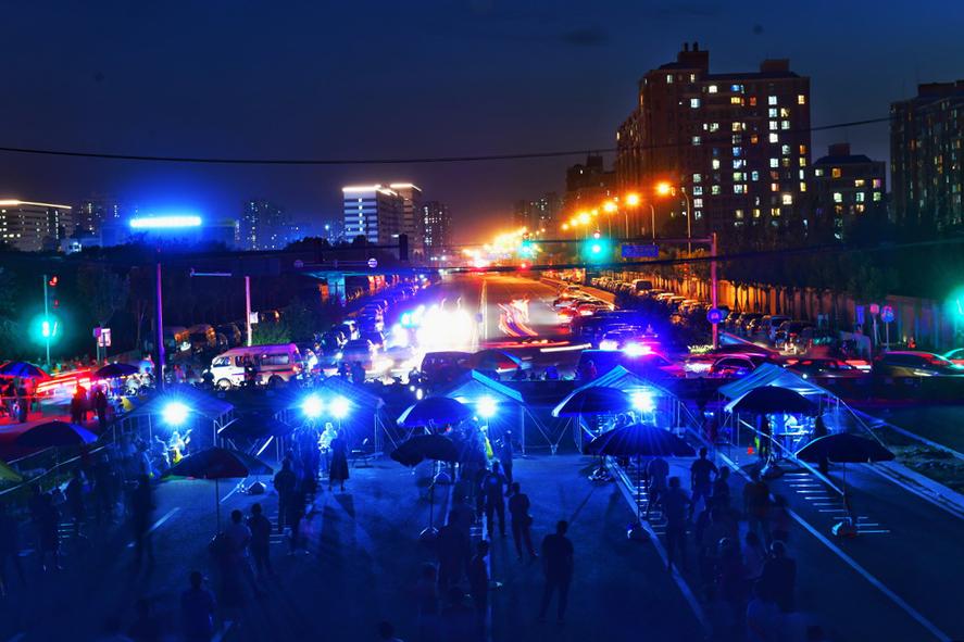北京丰台区新村街道的一处未开通的市政道路,已于6月14日凌晨临时改造成为一个核酸检测采样点。人民视觉 图