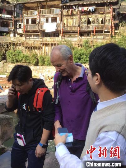图为英国驻重庆总领事馆总领事史云森(中)救人后离开事发现场。 江浪 摄