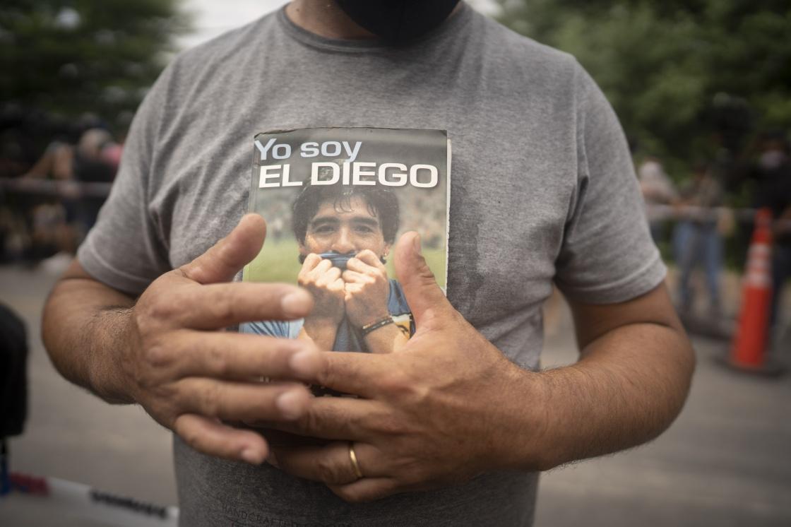 11月25日,在布宜诺斯艾利斯省蒂格雷,一名男子手捧马拉多纳的自传。新华社 图