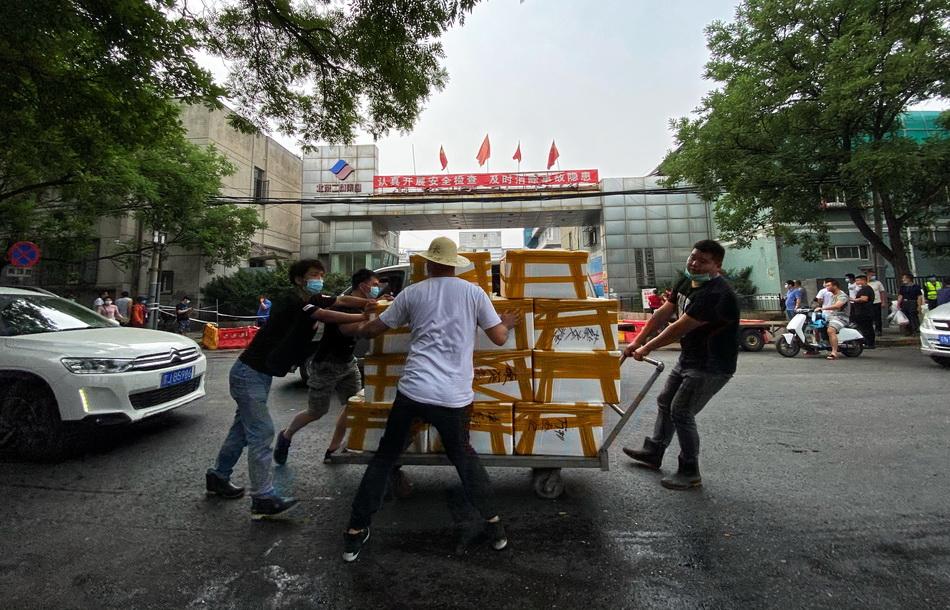 6月13日,北京京深海鲜市场门前贴出暂停营业的告示,大批商户正在有序撤走市场内的生鲜产品。人民视觉 图