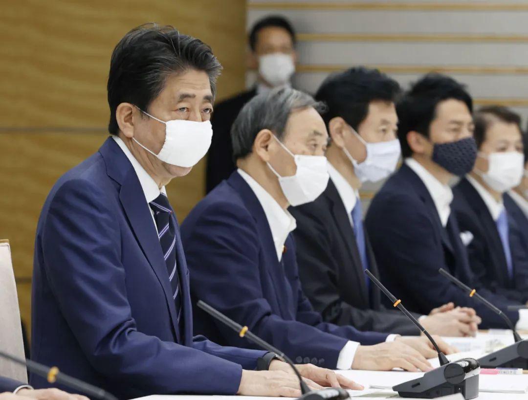 2020年5月21日,在日本东京,日本首相安倍晋三(左一)宣布,解除关西地区大阪府、京都府和兵库县三地的紧急状态,而包括东京都在内的首都圈4个都县以及北海道继续维持紧急状态。新华社/共同社