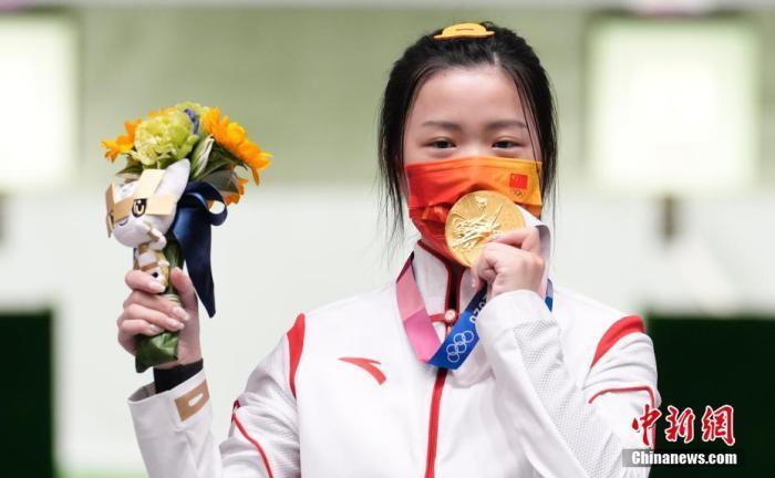 7月24日举行的东京奥运会女子10米气步枪决赛中,中国选手杨倩夺得冠军,为中国代表团揽入本届奥运会第一枚金牌。这也是本届东京奥运会诞生的首枚金牌。图为杨倩隔着口罩亲吻金牌。<a target='_blank' href='http://www.chinanews.com/'>中新社</a>记者 杜洋 摄