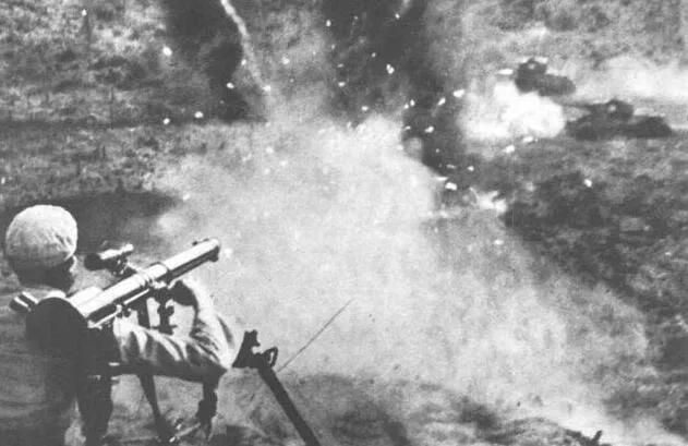 上图_ 志愿军在使用火箭筒攻击法国营坦克