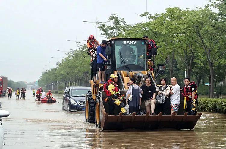 ▲7月21日,郑州,金水东路东四环桥下被困群众乘坐挖掘机前往安全地带。
