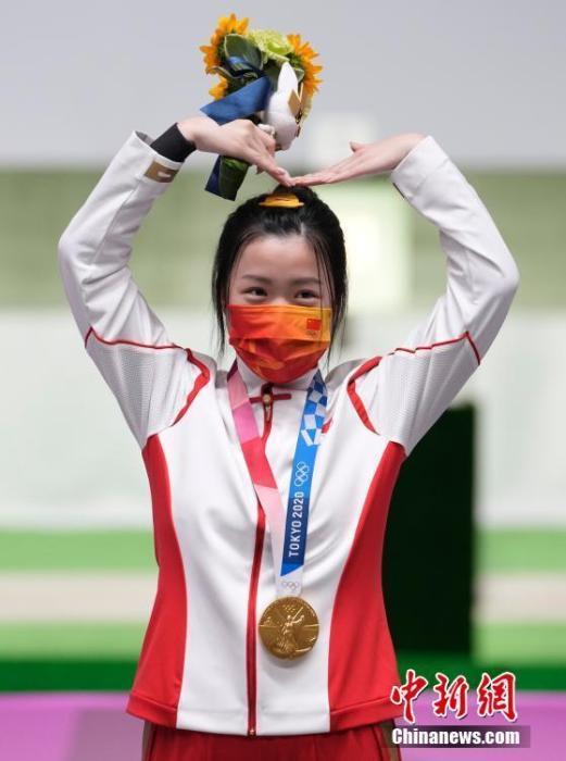 7月24日举行的东京奥运会女子10米气步枪决赛中,中国选手杨倩夺得冠军,为中国代表团揽入本届奥运会第一枚金牌。这也是本届东京奥运会诞生的首枚金牌。图为杨倩在领奖台上比出爱心手势。<a target='_blank' href='http://www.chinanews.com/'>中新社</a>记者 杜洋 摄