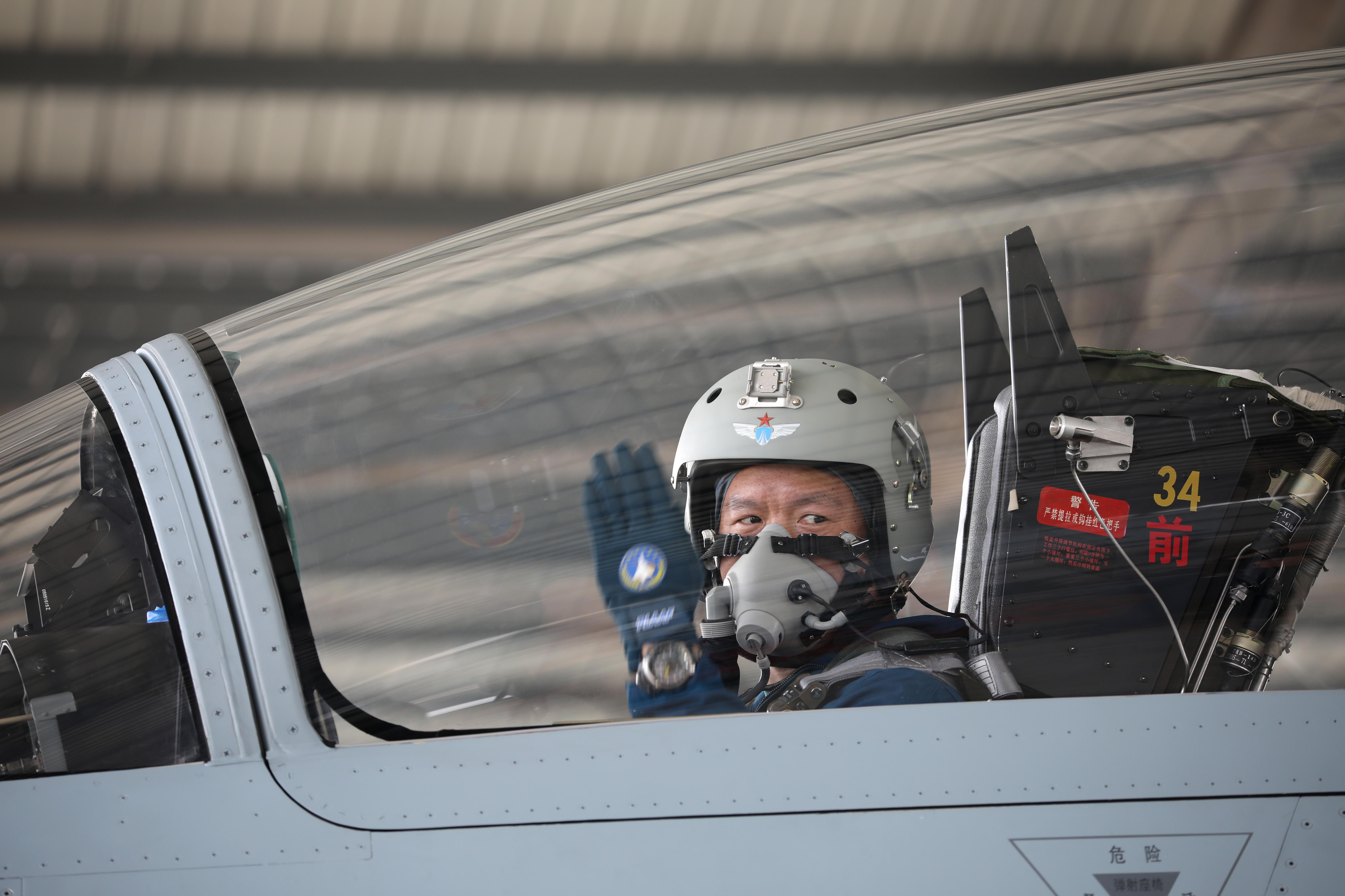↑2月23日,复飞重返战位的一等功空军飞行员王建东手势示意机组,准备滑出。黄演庄 摄