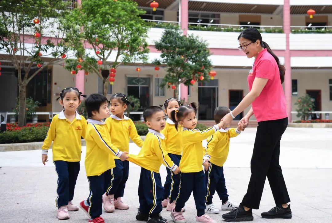 在广东茂名市社会福利中心,职工海连(右)在照顾院内儿童行走(4月28日摄)。