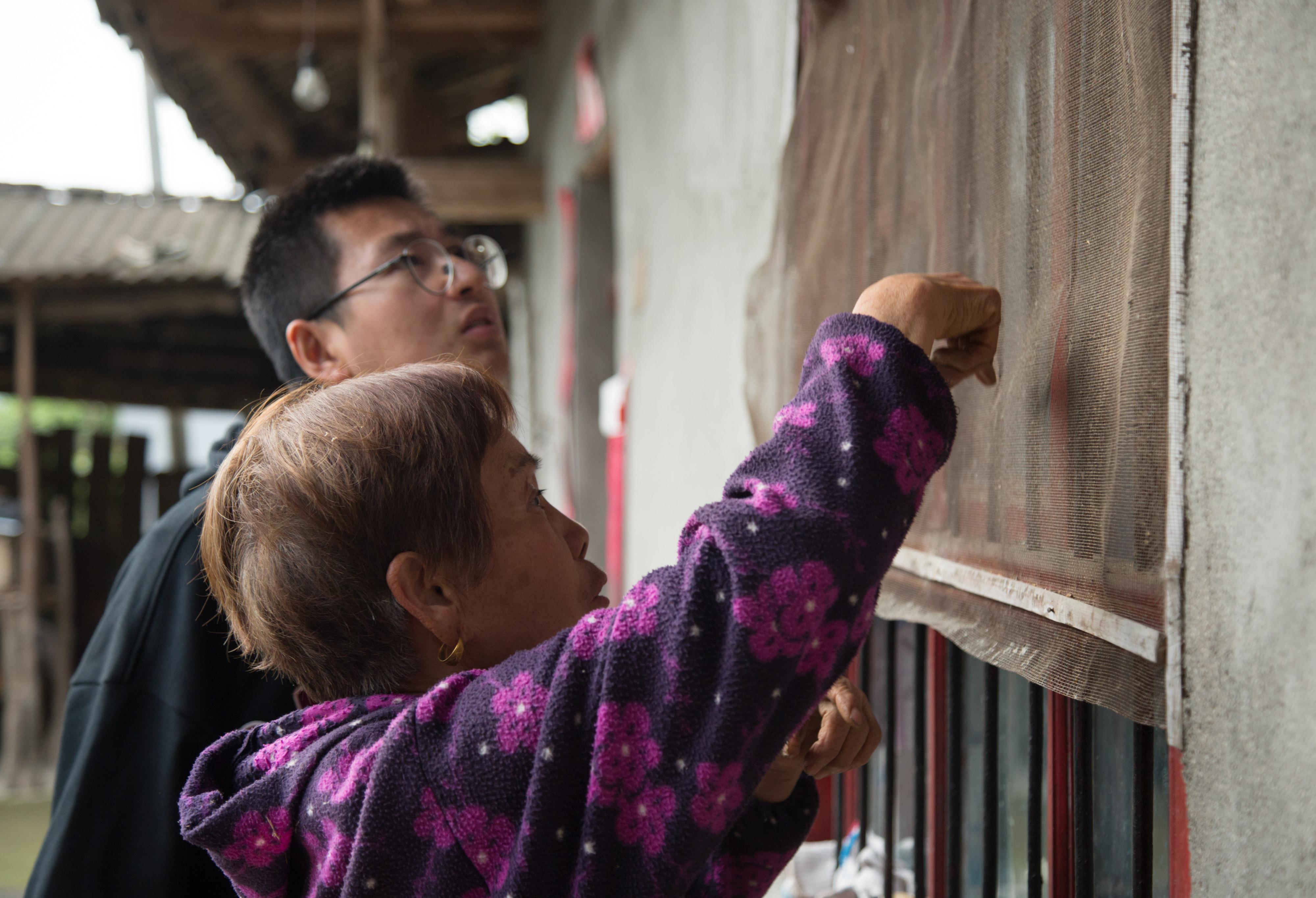 4月15日,在陕西省汉中市西乡县子午镇七星坝村,武轩羽(后)与村民王顺芳交流。
