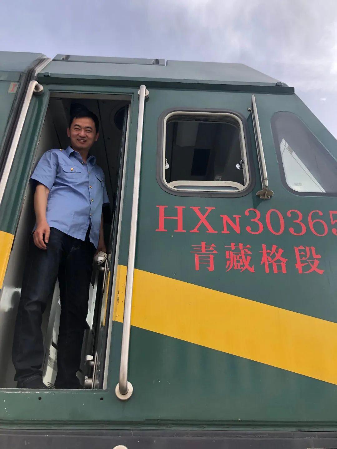 6月8日,格尔木机务段指导司机许宝平,站在青藏线火车头上。新京报记者 杜寒三 摄