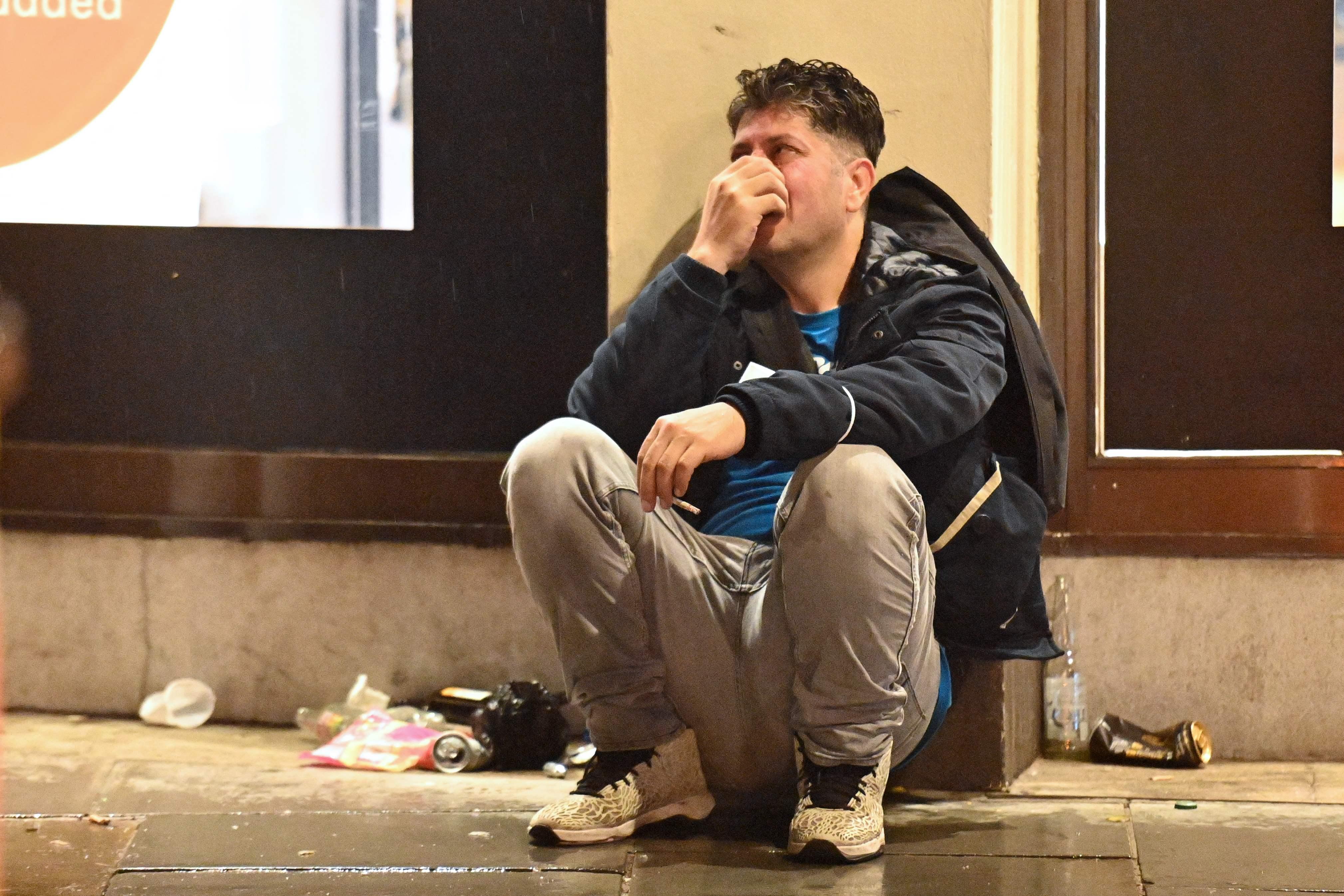 英格兰球迷坐在路边哭泣。