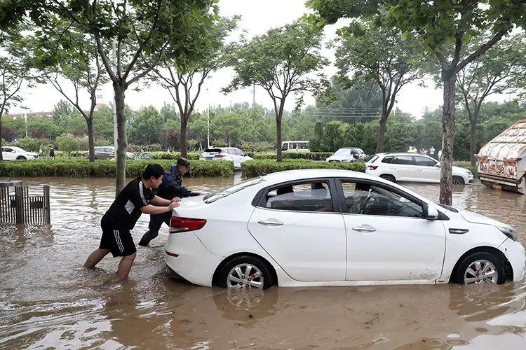 ▲7月21日,郑州,救援队员帮助市民推涉水车辆。