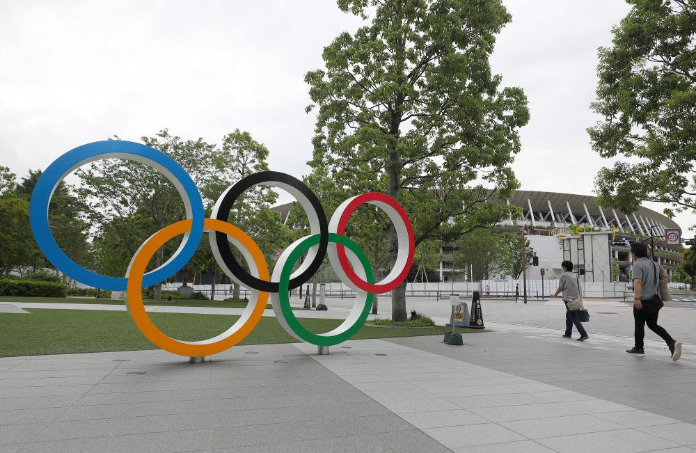 """2020年6月12日在日本东京拍摄的五环标志和东京奥运会主场馆""""国立竞技场""""一角。 新华社记者杜潇逸摄"""